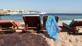 Wooden chair at the beach of background of blue sea and white yacht floats. Two empty wooden deck chairs on the beach on the chair are sunglasses and pareo that stock footage