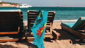 Wooden chair at the beach of background of blue sea and white yacht floats. Two empty wooden deck chairs on the beach on the chair are sunglasses and pareo that stock video