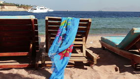 Wooden chair at the beach of background of blue sea and white yacht floats. Two empty wooden deck chairs on the beach on the chair are sunglasses and pareo that stock video footage