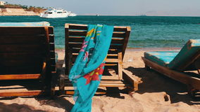 Wooden chair at the beach of background of blue sea and white yacht floats stock video