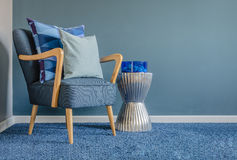 Wooden chair with blue color pillow on carpet Stock Image
