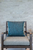 Wooden chair with blue pillow in living room with rock wall Royalty Free Stock Photography