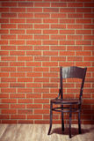 Wooden chair before brick wall Stock Photo