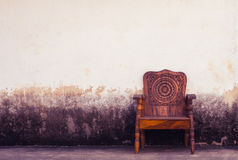 Wooden chair on concrete wall Stock Images