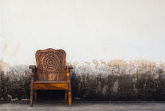 Wooden chair on concrete wall Royalty Free Stock Photos