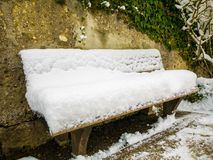 Wooden chair covered in snow in a mirabell garden.Austria Salzburg winter. stock photography