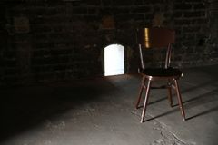 Wooden chair in a dark room stock photo