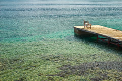 Wooden chair on fishing pier on Greek Dodecanese Royalty Free Stock Image