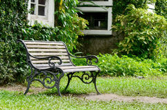 Wooden chair in garden on dingy light day Royalty Free Stock Photos