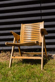Wooden chair on grass in front of black wall Royalty Free Stock Photography