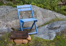Wooden chair and grill area. Blue painted wooden chair and grill area with rusty grillage Stock Photo