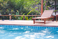 Wooden chair on Hotel swimming pool. Background Stock Image