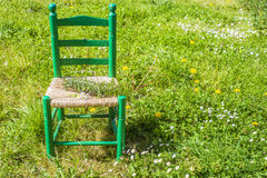 Wooden chair in the meadow Royalty Free Stock Image