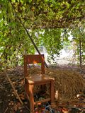 Wooden chair next to pile of hay under Bottle Gourd tunnel Stock Photography