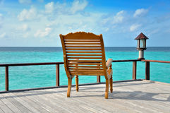 Wooden chair by the ocean Royalty Free Stock Images