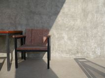 The wooden chair is placed in front of the cement wall with a shadow across royalty free stock photography