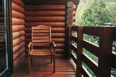 Wooden chair on porch of cabin among woods. cottage balcony with. View on forest in mountains. atmospheric moment. summer vacation. rural country relax time Royalty Free Stock Photos