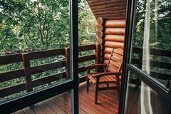 Wooden chair on porch of cabin among woods. cottage balcony with. View on forest in mountains. atmospheric moment. summer vacation. rural country relax time Stock Photography