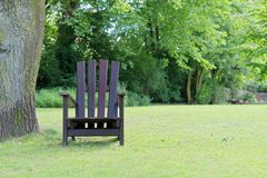 Wooden chair for relaxing on the green lawn. In a public park. `Planten un Blomen ` city garden in Hamburg, Germany royalty free stock photos