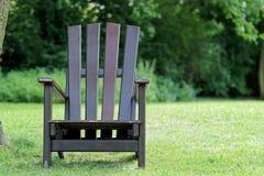 Wooden chair for relaxing on the green meadow. Closeup photo of wooden chair for relaxing on the green meadow in a public park. `Planten un Blomen ` city garden stock image