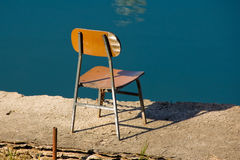 Wooden chair on river bank. Rear view of wooden chair on river bank with blue water in background Royalty Free Stock Photos