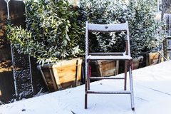 Wooden Chair on Snowy Porch. A wooden chair sitting on a porch after a heavy snowfall in the mountains Royalty Free Stock Images