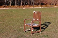A wooden chair stands on green grass. A wooden shabby chair stands on green grass stock image