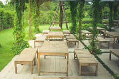Wooden chair and table in beautiful garden at outdoor. Autumn filter effect Stock Images