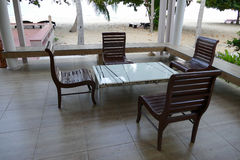 Wooden chair and white table near the beach Stock Photography