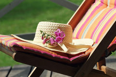 Wooden chair with women hat Stock Image