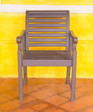 Wooden chair on yellow wall. Stock Images