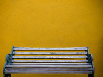 Wooden chair and yellow wall Stock Photos