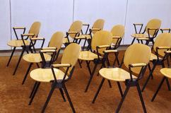 Wooden Chairs. Rows of empty wooden yellow chairs in a workshop room Stock Photos