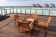 Wooden chairs at balcony with water villas background Royalty Free Stock Photos