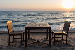 Wooden chairs on the beach at sunrise with a tropical sea Stock Images