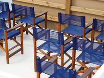 Wooden chairs with blue mesh upholstery stock photos