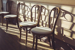 Wooden chairs in cafe. Interior with shade and shadow Stock Image