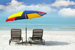Wooden chairs and colorful umbrella on beach Royalty Free Stock Photo