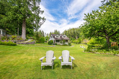 Wooden chairs with country home in background Stock Images