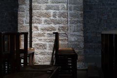 Wooden Chairs in a Dark Church, Subtle Lighting on Stone Wall Stock Images