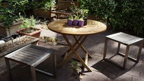 Wooden chairs and wooden deck table surrounded by flower beds in inner yard patio garden Royalty Free Stock Images