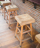 Wooden chairs with leather seat against red brick wall in coffee. The empty cafe Coffee shop, wooden chairs with leather seat near the bar against red/orange Royalty Free Stock Images