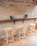 Wooden chairs with leather seat against red brick wall in coffee. The empty cafe Coffee shop, wooden chairs with leather seat near the bar against red/orange Stock Photos