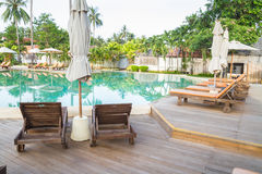 Wooden chairs on pool deck royalty free stock images