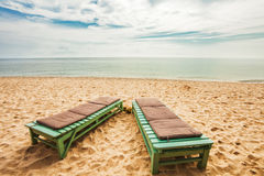 Wooden chairs on sand beach Stock Photo