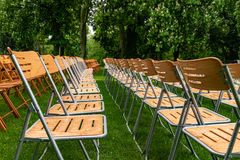 Wooden chairs stand outside in the park in the rain. Empty auditorium, green grass, trees and water drops stock photos