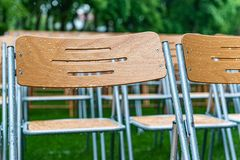 Wooden chairs stand outside in the park in the rain. Empty auditorium, green grass, waterdrops, closeup. Lot of wooden chairs stand outside in the park in the royalty free stock photos