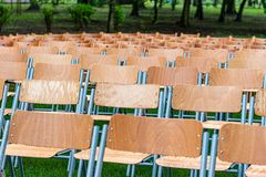 Wooden chairs stand outside in the park in the rain. Empty auditorium, green grass, waterdrops, closeup. Lot of wooden chairs stand outside in the park in the royalty free stock photography