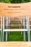 Wooden chairs stand outside in the park in the rain. Empty auditorium, green grass, waterdrops, closeup. Lot of wooden chairs stand outside in the park in the stock photos