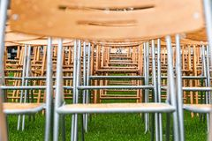 Wooden chairs stand outside in the park in the rain. Empty auditorium, green grass, waterdrops, closeup. Lot of wooden chairs stand outside in the park in the stock image